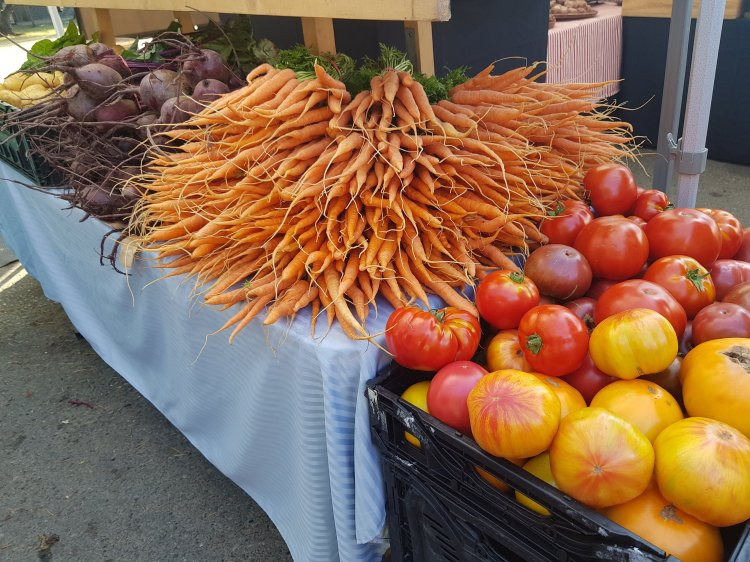 Heaps of organic beets, carrots, and heirloom tomatoes at a farmer's market