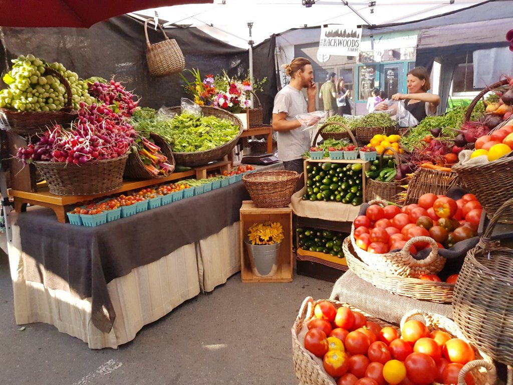 A vegetable stand at a farmer's market, with two vendors chatting happily behind their produce