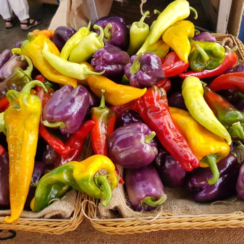 Yellow, red, purple, and green bell peppers piled up at a farmer's market